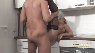 Older golden-haired woman is sucking a alt hard dong in the kitchen, in advance of getting screwed from behind